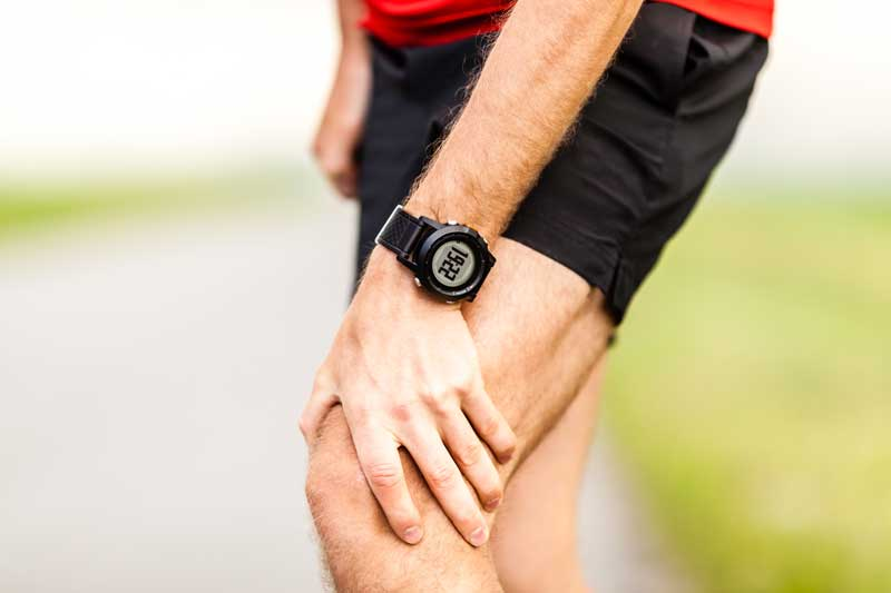 Runner holding sore leg, knee pain from running or exercising. Stretches for knee pain